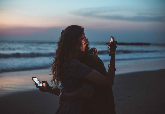 Couple hugging and using smartphone near sea on sunset 4555321 kopie